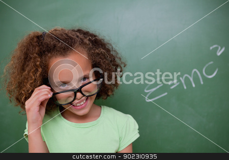 Smart schoolgirl looking above her glasses stock photo, Smart schoolgirl looking above her glasses in front of a blackboard by Wavebreak Media
