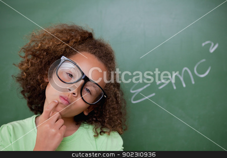 Smart schoolgirl thinking stock photo, Smart schoolgirl thinking in front of a blackboard by Wavebreak Media