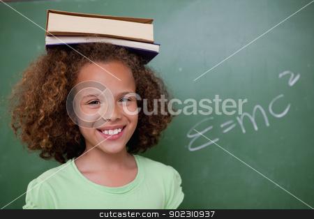 Happy schoolgirl holding her book on her head stock photo, Happy schoolgirl holding her book on her head in front of a blackboard by Wavebreak Media