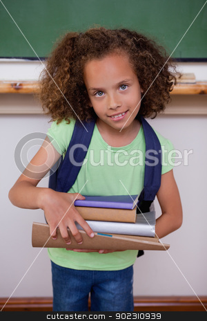 Portrait of a schoolgirl holding books stock photo, Portrait of a schoolgirl holding books in a classroom by Wavebreak Media