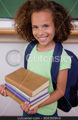 Portrait of a schoolgirl holding her books stock photo, Portrait of a schoolgirl holding her books in a classroom by Wavebreak Media