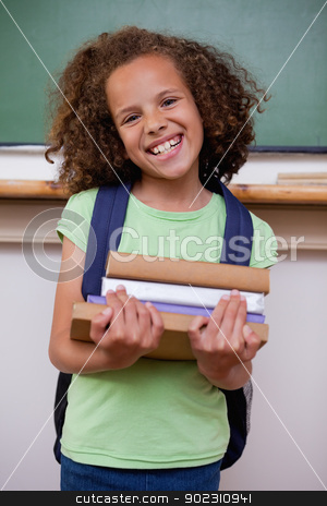 Portrait of a smiling schoolgirl holding her books stock photo, Portrait of a smiling schoolgirl holding her books in a classroom by Wavebreak Media
