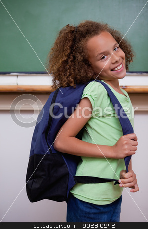 Portrait of a schoolgirl showing her backpack stock photo, Portrait of a schoolgirl showing her backpack in a classroom by Wavebreak Media