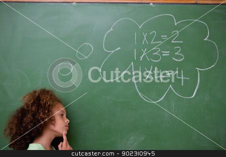 Schoolgirl thinking about algebra stock photo, Schoolgirl thinking about algebra in front of a blackboard by Wavebreak Media