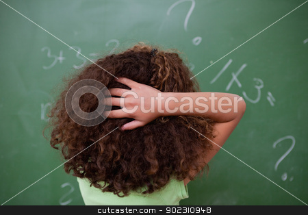 Schoolgirl thinking about algebra while scratching the back of h stock photo, Schoolgirl thinking about algebra while scratching the back of her head in front of a blackboard by Wavebreak Media