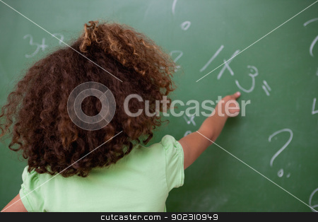 Schoolgirl pointing at an addition stock photo, Schoolgirl pointing at an addition on a blackboard by Wavebreak Media
