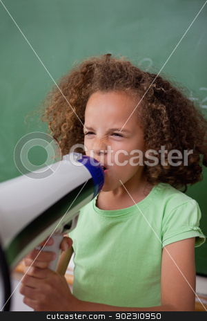 Portrait of a schoolgirl screaming through a megaphone stock photo, Portrait of a schoolgirl screaming through a megaphone in a classroom by Wavebreak Media
