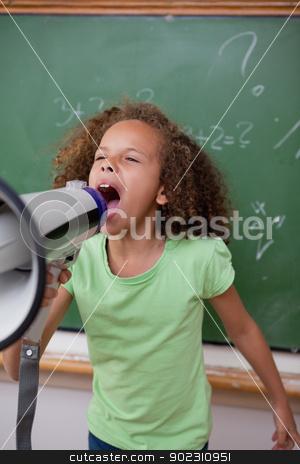 Portrait of a cute schoolgirl screaming through a megaphone stock photo, Portrait of a cute schoolgirl screaming through a megaphone in a classroom by Wavebreak Media