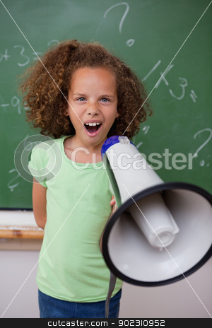 Portrait of a young schoolgirl screaming through a megaphone stock photo, Portrait of a young schoolgirl screaming through a megaphone in a classroom by Wavebreak Media