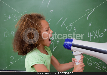 Side view of a schoolgirl screaming through a megaphone stock photo, Side view of a schoolgirl screaming through a megaphone in a classroom by Wavebreak Media