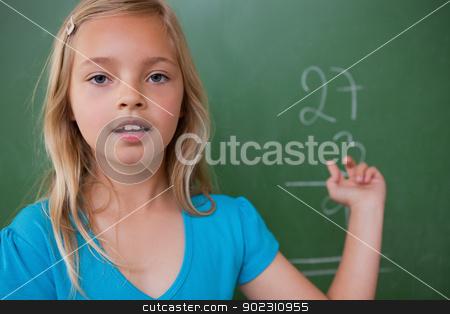 Little schoolgirl showing her result stock photo, Little schoolgirl showing her result on a blackboard by Wavebreak Media