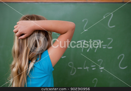 Little schoolgirl thinking while scratching the back of her head stock photo, Little schoolgirl thinking while scratching the back of her head in front of a blackboard by Wavebreak Media