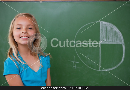 Smiling schoolgirl learning the divisions stock photo, Smiling schoolgirl learning the divisions on a blackground by Wavebreak Media