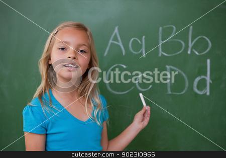 Smiling schoolgirl showing letters stock photo, Smiling schoolgirl showing letters on a blackboard by Wavebreak Media