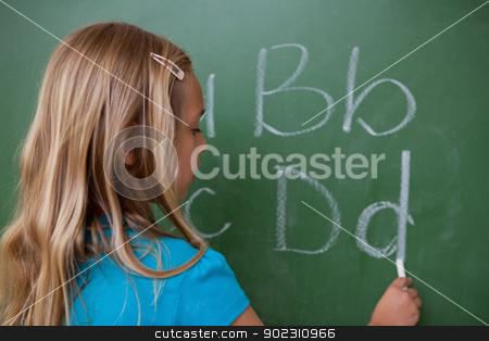 Schoolgirl writing letters stock photo, Schoolgirl writing letters on a blackboard by Wavebreak Media