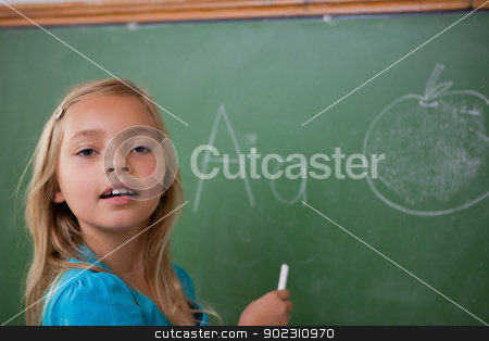 Young schoolgirl learning the alphabet stock photo, Young schoolgirl learning the alphabet on a blackboard by Wavebreak Media