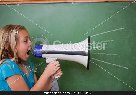 Young schoolgirl screaming through a megaphone stock photo, Young schoolgirl screaming through a megaphone in front of blackboard by Wavebreak Media