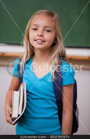 Portrait of a blonde schoolgirl holding her books stock photo, Portrait of a blonde schoolgirl holding her books in a classroom by Wavebreak Media