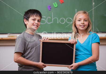 Pupils holding a school slate stock photo, Pupils holding a school slate in a classroom by Wavebreak Media