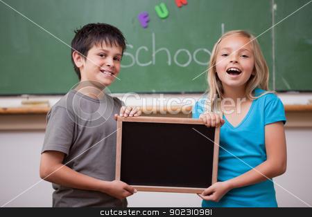 Happy pupils holding a school slate stock photo, Happy pupils holding a school slate in a classroom by Wavebreak Media