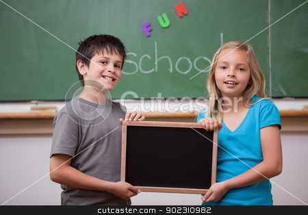 Smiling pupils holding a school slate stock photo, Smiling pupils holding a school slate in a classroom by Wavebreak Media