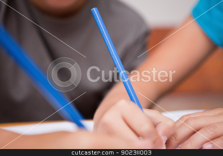 Close up of two arms holding pens stock photo, Close up of two arms holding pens in a classroom by Wavebreak Media