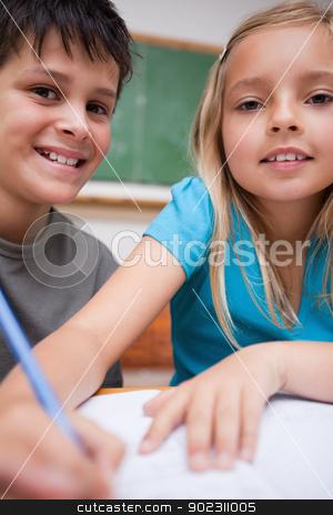 Portrait of two children writing stock photo, Portrait of two children writing in a classroom by Wavebreak Media