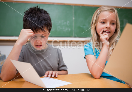 Two children reading stock photo, Two children reading in a classroom by Wavebreak Media