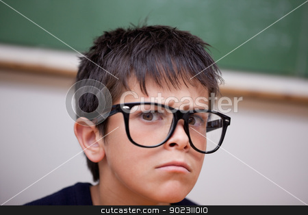 Close up of a serious schoolboy stock photo, Close up of a serious schoolboy in a classroom by Wavebreak Media