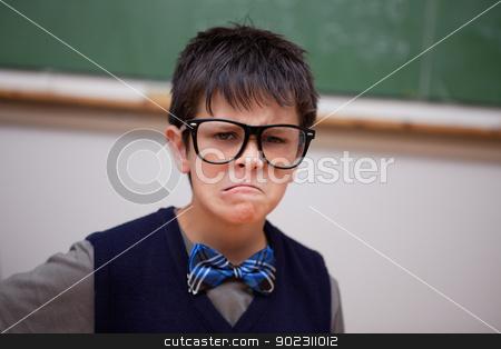 Grumpy schoolboy posing stock photo, Grumpy schoolboy posing in a classroom by Wavebreak Media