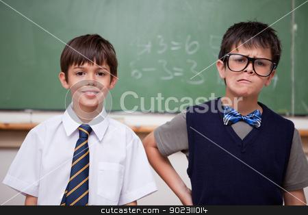 Schoolboys posing in front of a chalkboard stock photo, Schoolboys posing in front of a chalkboard in a classroom by Wavebreak Media