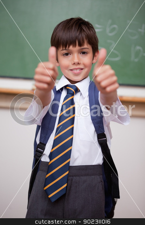 Portrait of a smiling schoolboy with the thumbs up stock photo, Portrait of a smiling schoolboy with the thumbs up in a classroom by Wavebreak Media