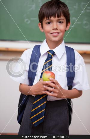Portrait of a schoolboy holding an apple stock photo, Portrait of a schoolboy holding an apple in a classroom by Wavebreak Media