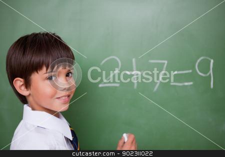 Smiling schoolboy writing an addition stock photo, Smiling schoolboy writing an addition on a chalkboard by Wavebreak Media