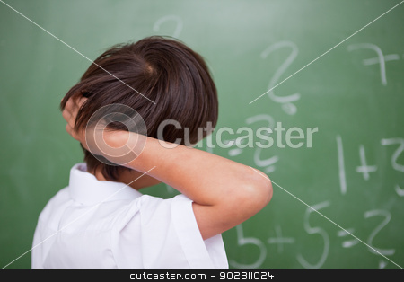 Schoolboy thinking while scratching the back of his head stock photo, Schoolboy thinking while scratching the back of his head in front of a chalkboard by Wavebreak Media
