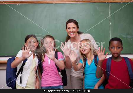 Schoolteacher and her pupils waving at the camera stock photo, Schoolteacher and her pupils waving at the camera in a classroom by Wavebreak Media