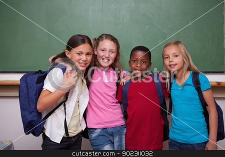 Classmates posing together stock photo, Classmates posing together in a classroom by Wavebreak Media