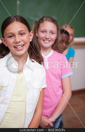 Portrait of classmates posing in a row stock photo, Portrait of classmates posing in a row in a classroom by Wavebreak Media