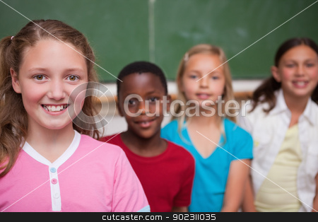 Classmates posing in a row stock photo, Classmates posing in a row in a classroom by Wavebreak Media