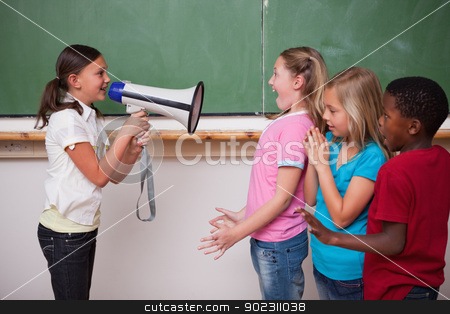 Schoolgirl screaming through a megaphone to her classmates stock photo, Schoolgirl screaming through a megaphone to her classmates in a classroom by Wavebreak Media
