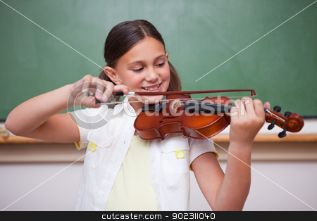 Schoolgirl playing the violin stock photo, Schoolgirl playing the violin in a classroom by Wavebreak Media