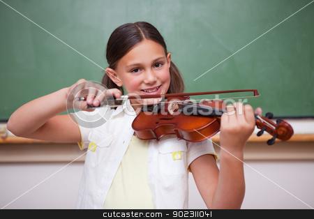 Smiling schoolgirl playing the violin stock photo, Smiling schoolgirl playing the violin in a classroom by Wavebreak Media