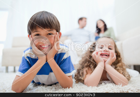 Kids lying on the carpet with parents sitting behind them stock photo, Young kids with lying on the carpet with parents sitting behind them by Wavebreak Media