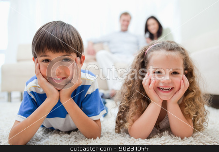 Happy kids lying on the carpet with parents behind them stock photo, Happy smiling kids lying on the carpet with parents behind them by Wavebreak Media