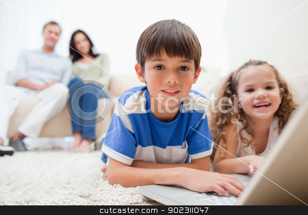 Cute kids playing computer games on laptop stock photo, Cute kids playing computer games on laptop together by Wavebreak Media
