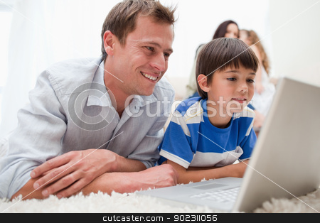 Son and father using laptop on the carpet stock photo, Son and father using laptop together on the carpet by Wavebreak Media