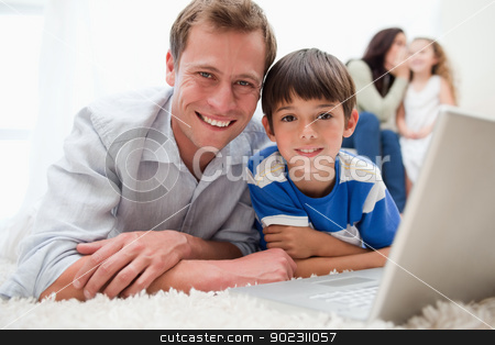 Smiling son and dad using laptop on the carpet stock photo, Smiling son and dad using laptop together on the carpet by Wavebreak Media