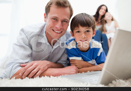 Boy with his father using laptop on the carpet stock photo, Boy with his father using laptop together on the carpet by Wavebreak Media