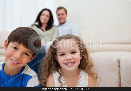 Family sitting in the living room stock photo, Smiling family sitting in the living room by Wavebreak Media