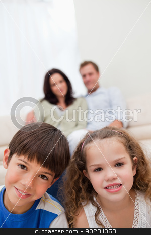 Children sitting in the living room with parents behind them stock photo, Children sitting in the living room with their parents behind them by Wavebreak Media